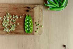 Green string of peas on wooden kitchen stock images