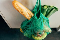 Green string shopping bag hanging on a hook in the kitchen. Green string shopping bag with vegetables, fruits and bread hanging on a hook in the kitchen Royalty Free Stock Photos