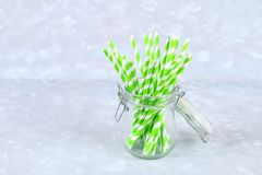 Green striped paper disposable tubes in a jar on a gray background. Green striped paper disposable tubes in a jar on a gray background Royalty Free Stock Photography