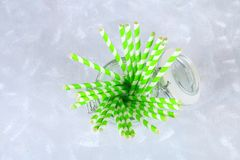 Green striped paper disposable tubes in a jar on a gray background. Green striped paper disposable tubes in a jar on a gray background Royalty Free Stock Images