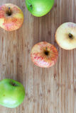 Green and striped pink apples on a wooden background Stock Photo