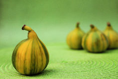 Green Stripes. Juicy fresh striped figs on green background Stock Photos