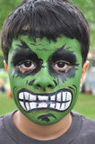 Green and Strong Little Boy. A cute little boy has his face painted like Hulk, the famous character of Hollywood stock images