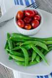 Green sugar beans and Cherry tomatoes. Sugar Beans steamed and plated next to fresh cherry tomatoes royalty free stock image