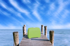 Green suitcase parked on the pier Stock Image