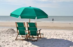 Green sun chairs and umbrella Stock Photo
