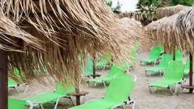 Green sunbeds and umbrellas made of reed on a beach royalty free stock photo