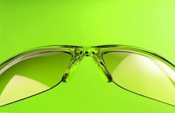 Green sunglasses. A pair of sunglasses over green bacground royalty free stock images