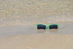 Green sunglasses on the wet sand Royalty Free Stock Photography