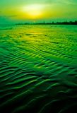 Green sunset. Seascape during sunset, focus on sand waves Stock Photo