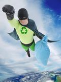 Eco superhero. Green superhero flying away from Earth with bag of trash helping to keep the planet clean Stock Photos