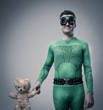 Green superhero holding a teddy bear Stock Photography