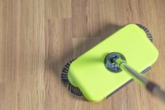 Green sweeper is cleaning wooden floo Stock Photos