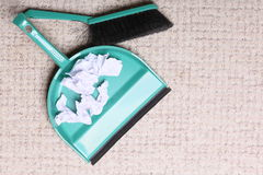 Green sweeping brush dustpan with garbage, housework. Green sweeping brush and dustpan for house work with garbage papers on floor indoors. Cleaning Royalty Free Stock Photography