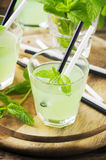 Green sweet cocktail with mint and ice on the wooden table Stock Photos