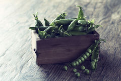 Green sweet peas in wooden box on brown wood surface Stock Photography