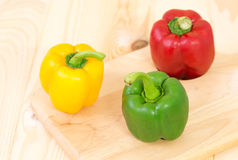 Green sweet peper on wooden plate Stock Images