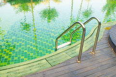 Green swimming pool with teak wood flooring Stock Image