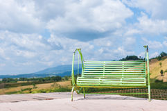 Green swing. Old green swing with cloudy blackground Royalty Free Stock Photography