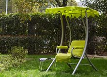 Green swing chair on the lawn in the garden.  Royalty Free Stock Images