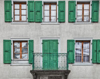 Green Swiss Window Shutter and Window Pane. Traditional green Swiss window shutters on medieval building wall with a small balcony Stock Images