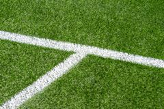 Green synthetic artificial grass soccer sports field with white corner stripe line stock photo