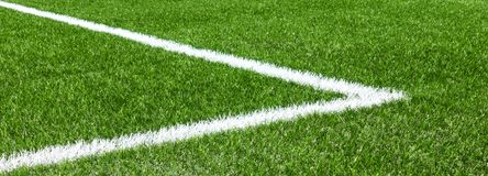 Green synthetic artificial grass soccer sports field with white corner stripe line.  stock images