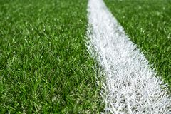 Green synthetic artificial grass soccer sports field with white stripe line.  stock photography
