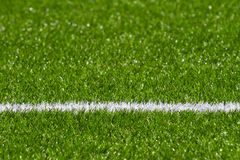 Green synthetic grass soccer sports field with white stripe line. Green synthetic grass soccer football sports field with white stripe line. Top view stock photography