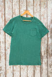 Green t-shirt with pocket on hanger Stock Photos