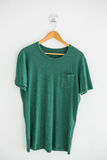 Green t-shirt with pocket on hanger Royalty Free Stock Image