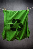Green t shirt with recycle symbol hanging on rope to dry. Attached with clothes pins Stock Photos