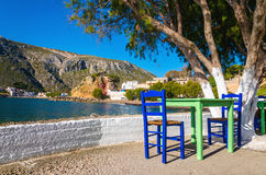 Green table with blue chairs. And typical white wall in romantic Greek bay on sunny day, Greece Royalty Free Stock Photos