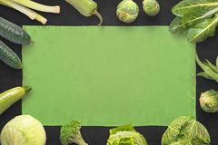 Green table cloth on black board surrounded with green vegetables. Flat lay composition Royalty Free Stock Photography