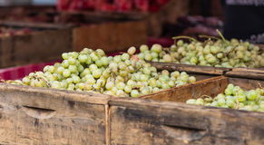 Green Table Grapes. Old wooden crates filled with green table grapes at a farmer's market royalty free stock images
