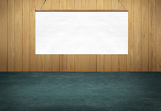 Green table with hanging white poster sign on wooden wall Royalty Free Stock Photography