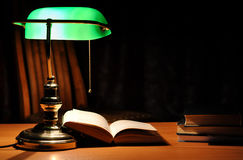 Green table lamp and opened book Royalty Free Stock Photos