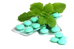 Green tablets. In packaging covered with green herbal leaves close up on white background Stock Photography