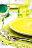 Green tableware and cutlery and white tablecloth set at an outdo. Or table catering event with transparent wine glass. Home outdoor living Royalty Free Stock Photo