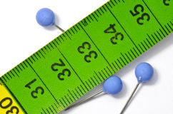 Green tailor measuring tape and pins Royalty Free Stock Photo