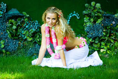 Green tale. Pretty Hawaii lady sitting on green grass Stock Photography