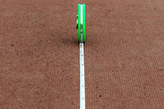 Green tape measure lying on a red running track stadium Royalty Free Stock Images