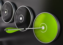 Green target and arrow - dart board. Many targets plus one green target over a black background, an arrow hit the center of the green dart board Stock Photography