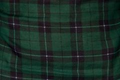 Green tartan ornament on fabric. Surface of green tartan ornament, photo of texture Royalty Free Stock Image