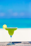 Green tasty cocktail on tropical white beach Stock Photo