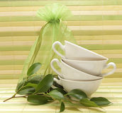 Green tea. Porcelain cups, green leaves and a bag of tea on the background of a striped mat Royalty Free Stock Image