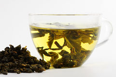 Green tea. Leaves of green tea and the clear glass cup of hot boiled tea on the white Stock Image
