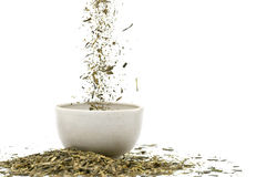 Green tea. Falling dried green tea leaves over white background stock image