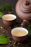 Green tea. Pouring green tea in cup Royalty Free Stock Images
