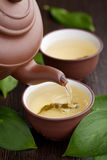 Green tea. Pouring into cup Stock Images